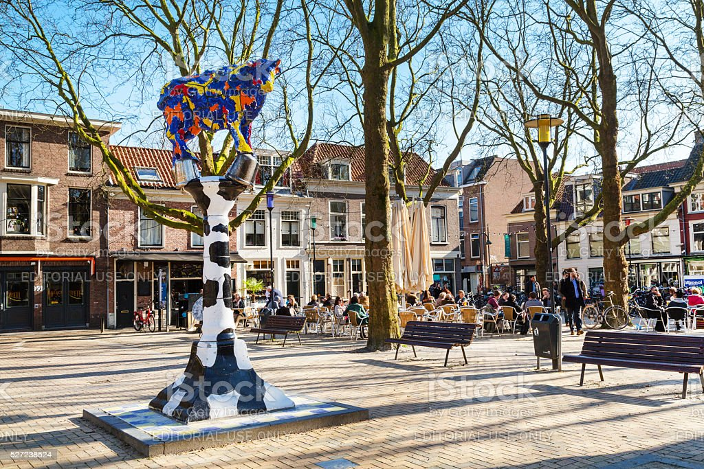 Colorful cow sculpture, square, people in cafe,  Delft, Holland stock photo