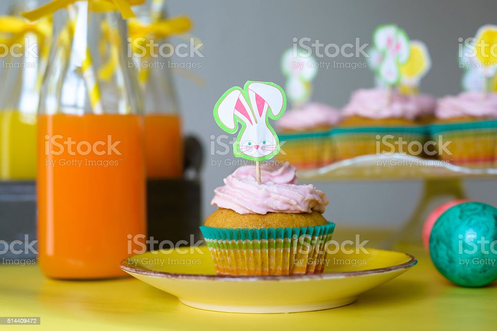 Colorful cupcake decorated with bunny picker on the yellow plate stock photo