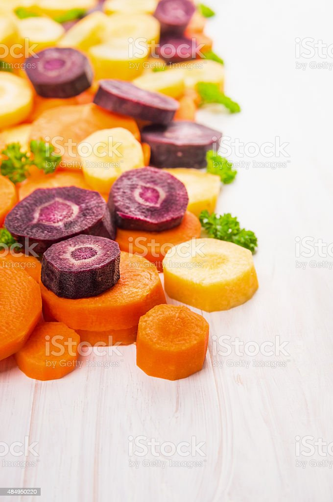 colorful cutting carrots on white wooden background stock photo