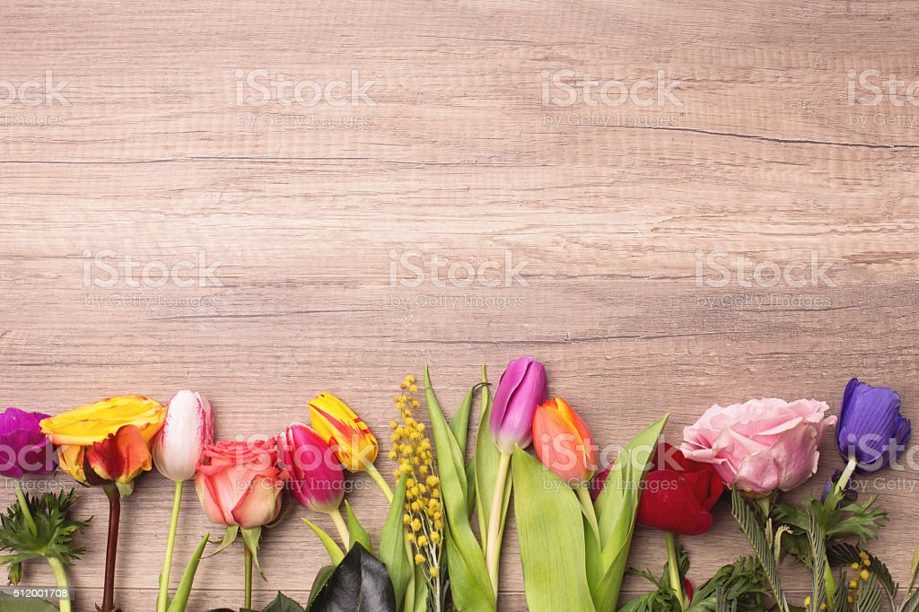 Colorful different kinds of flowers in line on wooden background stock photo