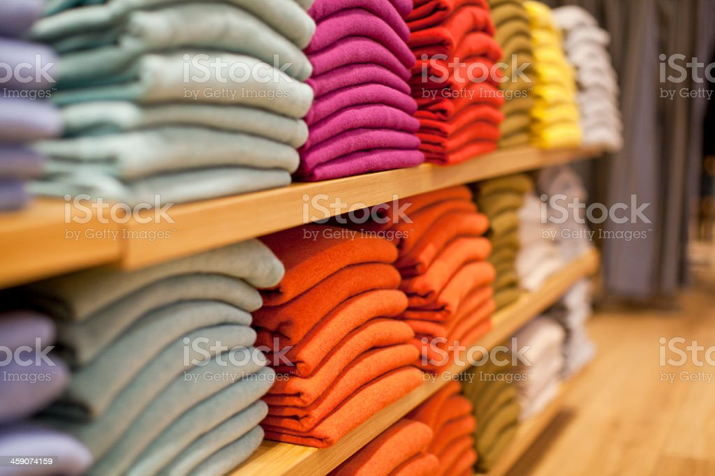 Colorful display of sweaters on shelf in store stock photo