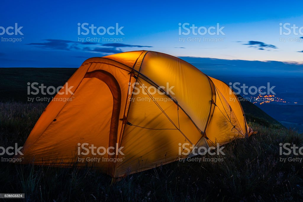 Colorful dome tent illuminated at sunset on summer mountain peak stock photo