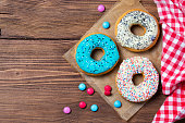 Colorful donuts and smarties on wooden table