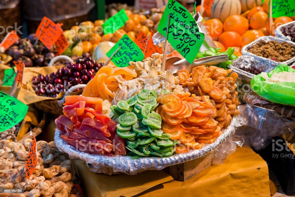 Colorful dried fruits and vegetables from organic agriculture exhibited in a italian market - dehydrated dried fruit 25 euro per kilogram written on green card stock photo