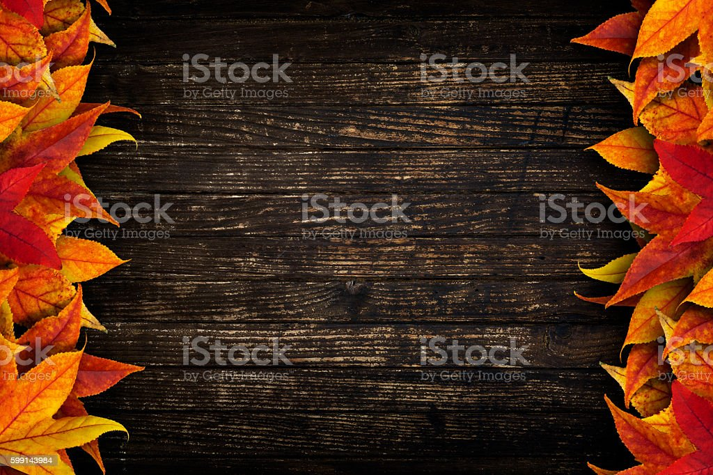 Colorful dried leaves on grunge brown wooden background stock photo