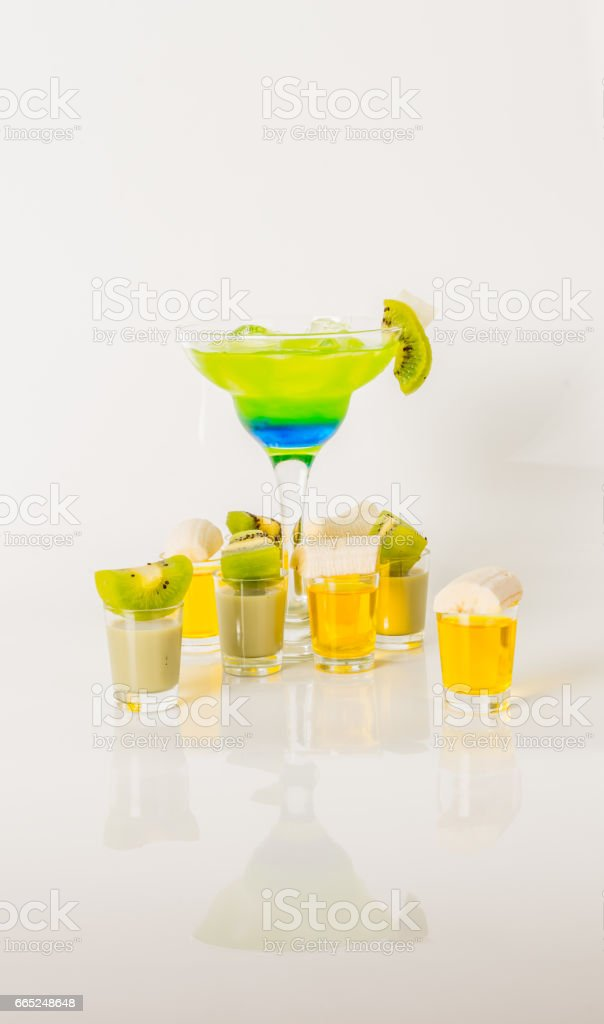 Colorful drink in a margarita glass, blue and green combination, many drinks in a shotglass stock photo