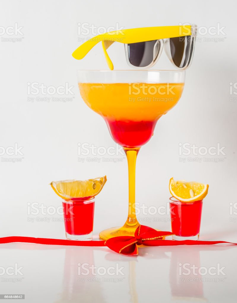 Colorful drink in a margarita glass, red and orange combination, two drinks in a shot glass, red bow stock photo