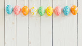 Colorful easter eggs hanging on rustic wooden white background