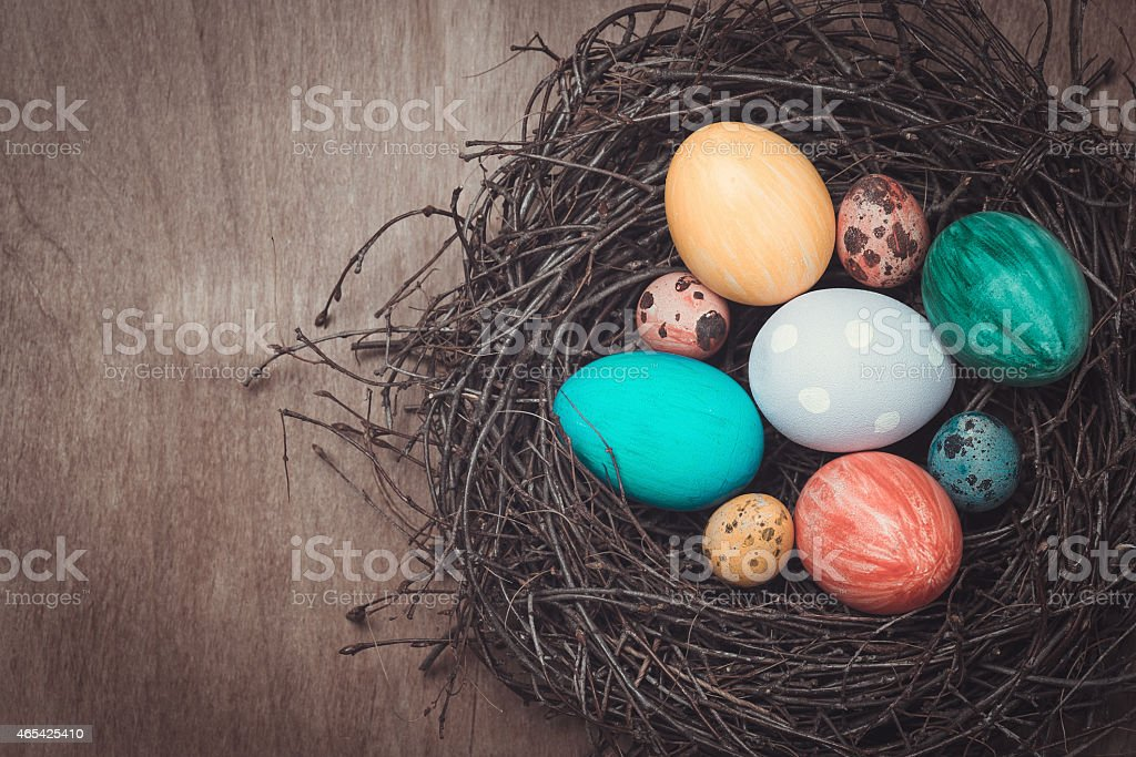 Colorful Easter eggs in a nest in rustic style stock photo