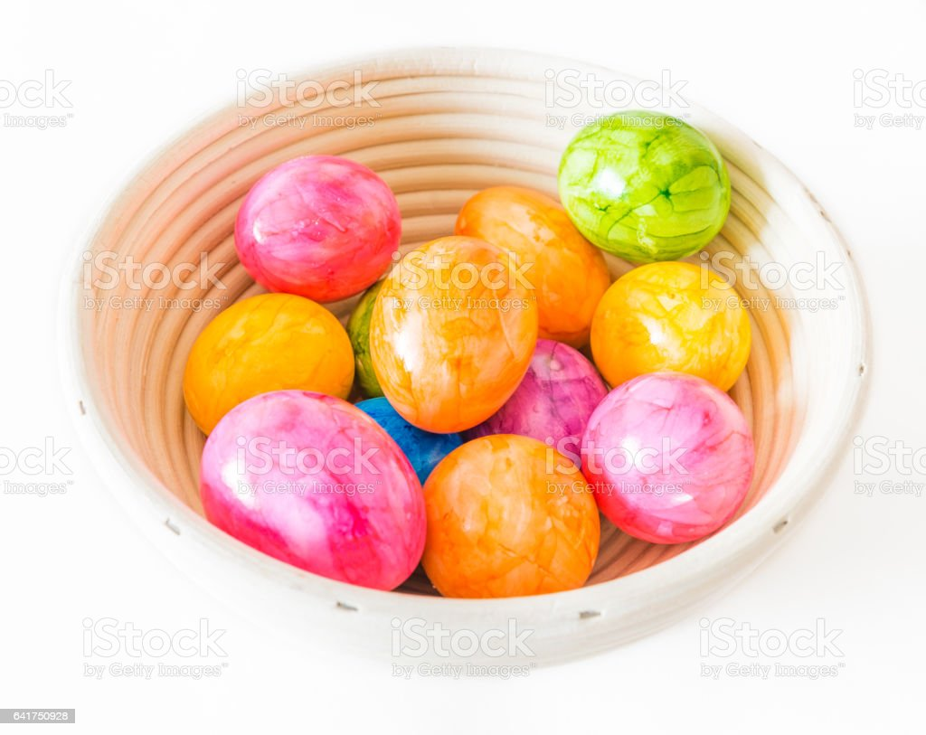 Colorful Easter eggs in a wooden bowl and white background stock photo