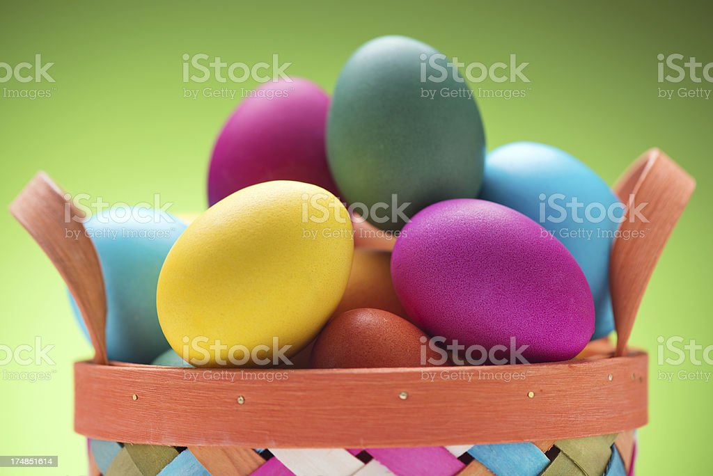 Colorful Easter Eggs in Basket on green background royalty-free stock photo