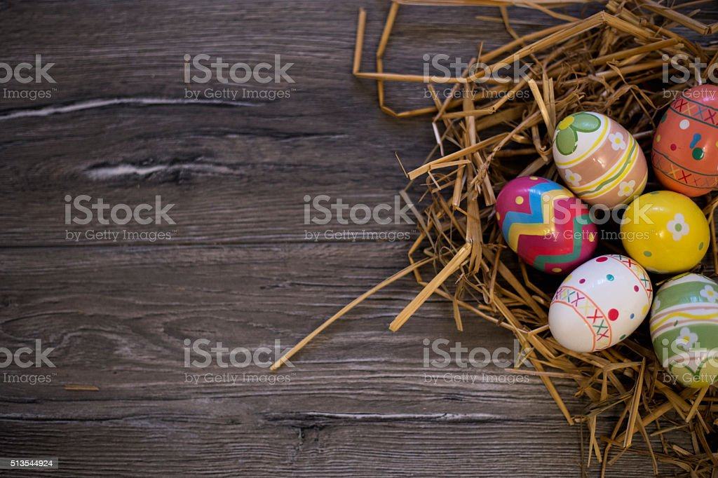 Colorful easter eggs in straw nest on a wooden table stock photo