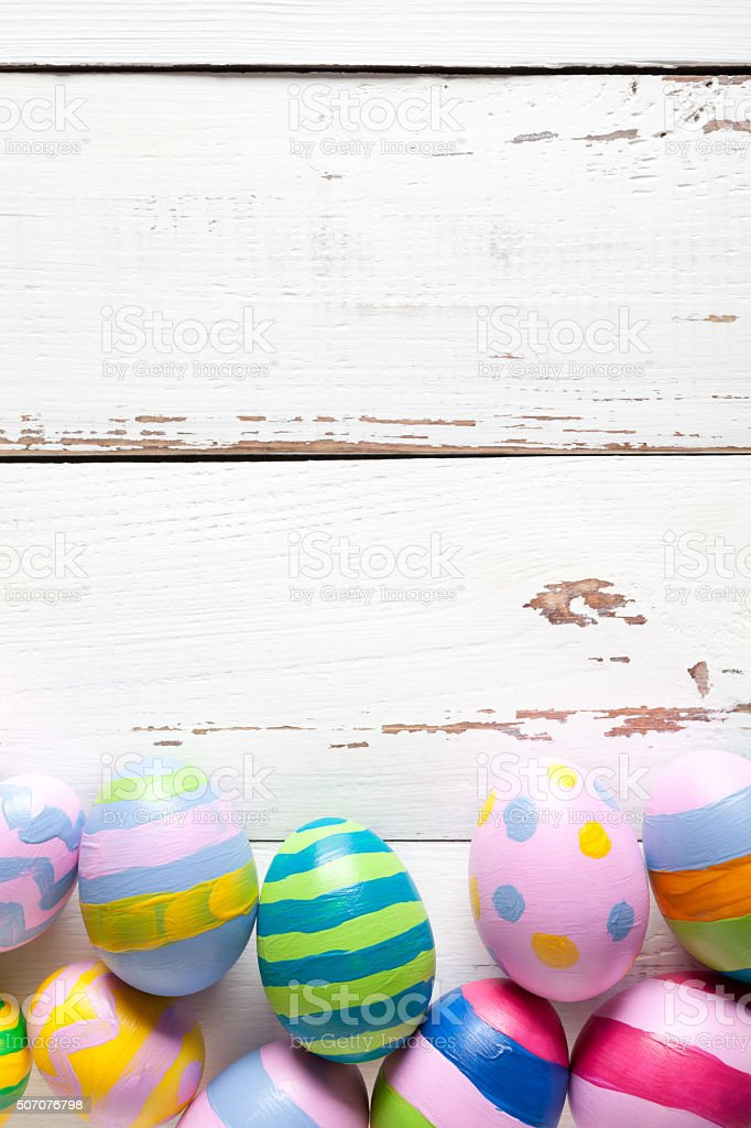 Colorful easter eggs on white wooden table stock photo