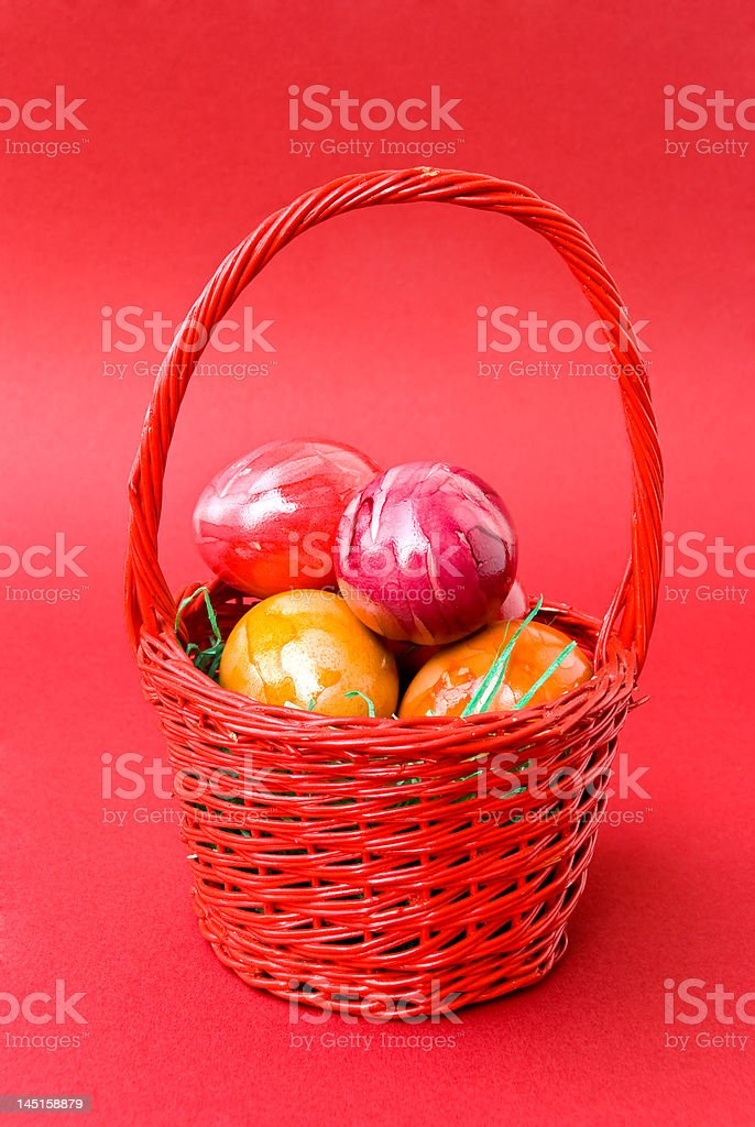 colorful eastern eggs in red basket royalty-free stock photo