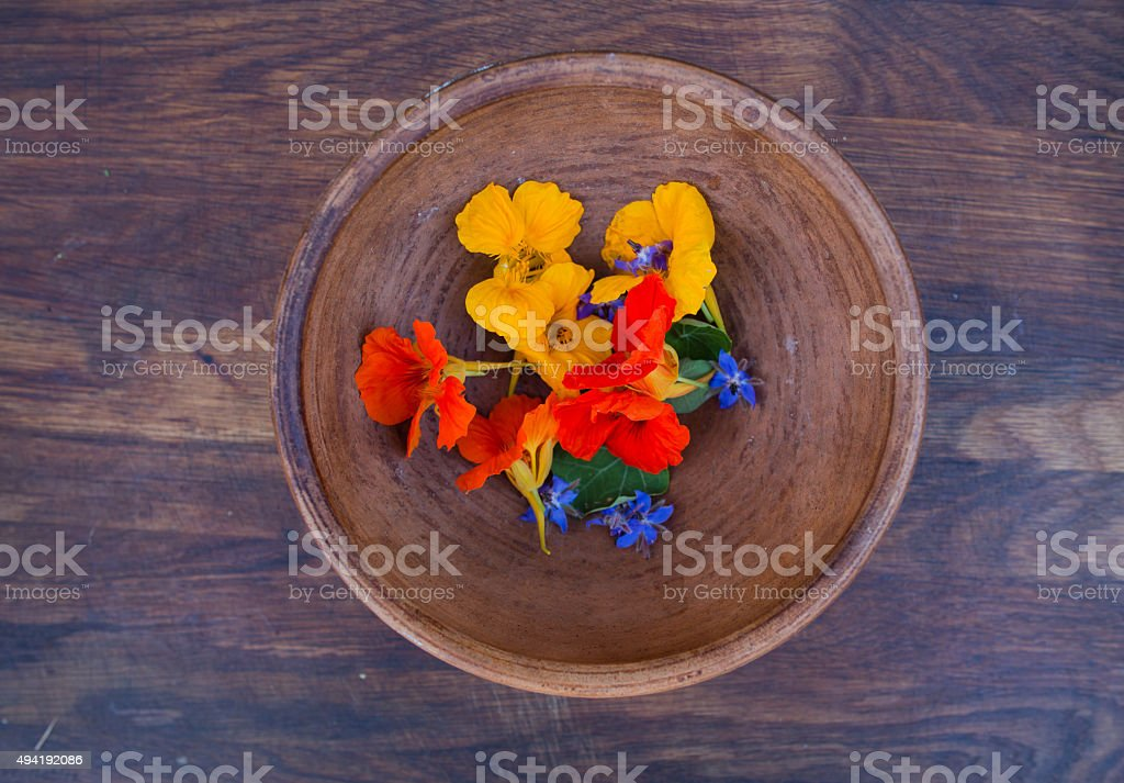 Colorful edible flowers in clay bowl on wooden background stock photo