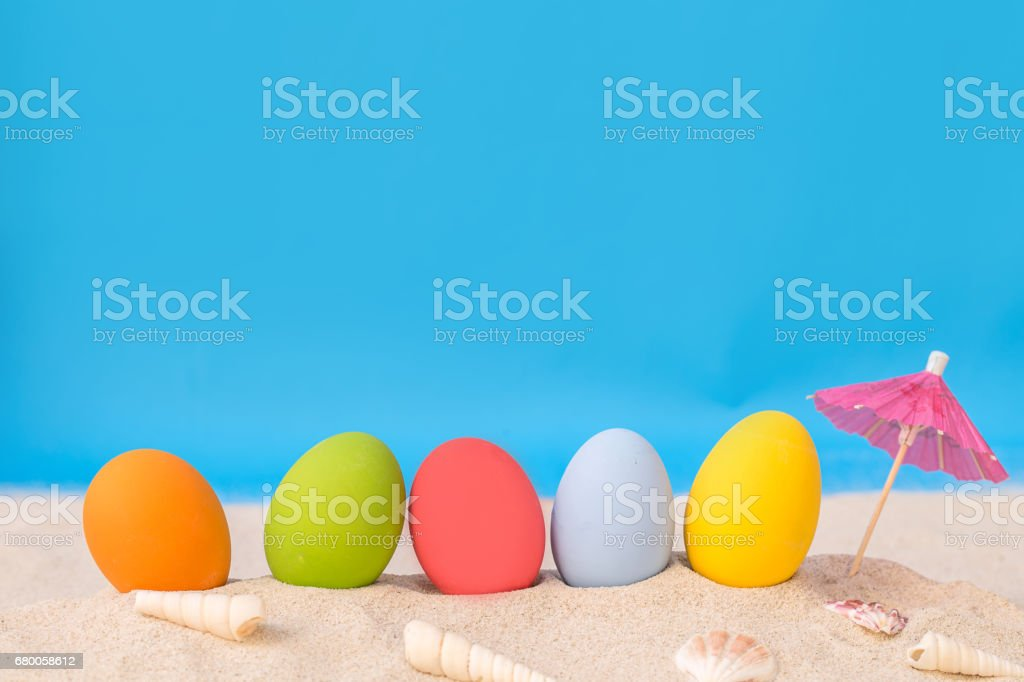 colorful eggs on white sand beach over cloudy sky stock photo