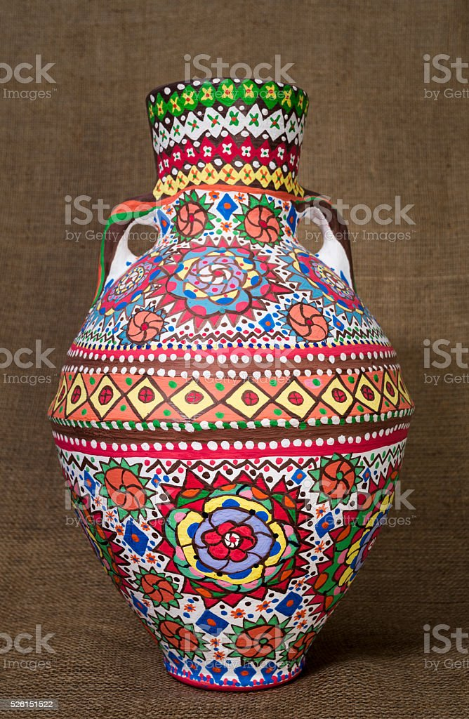 Colorful Egyptian handcrafted artistic ornate pottery jar on sackcloth background stock photo