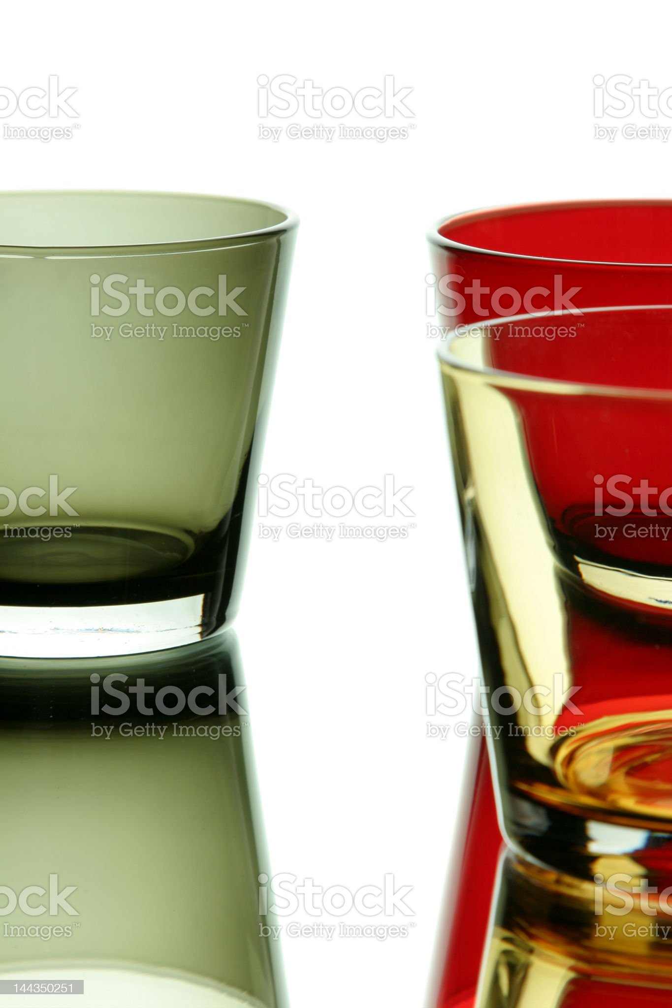 Colorful empty glass over a white reflective background royalty-free stock photo
