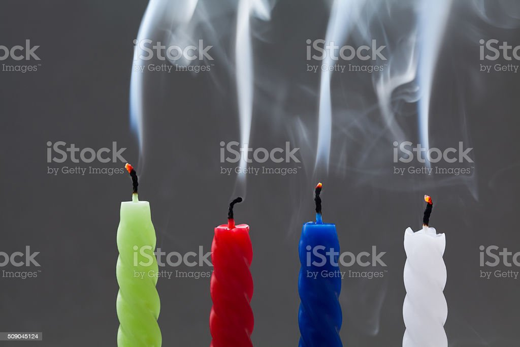 Colorful extinguished candles with white smoke on gray background. four stock photo