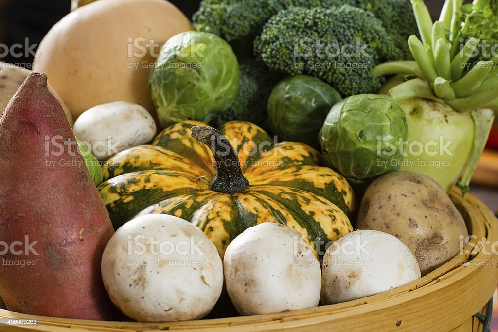 Colorful Fall Vegetables fill a wicker basket. stock photo