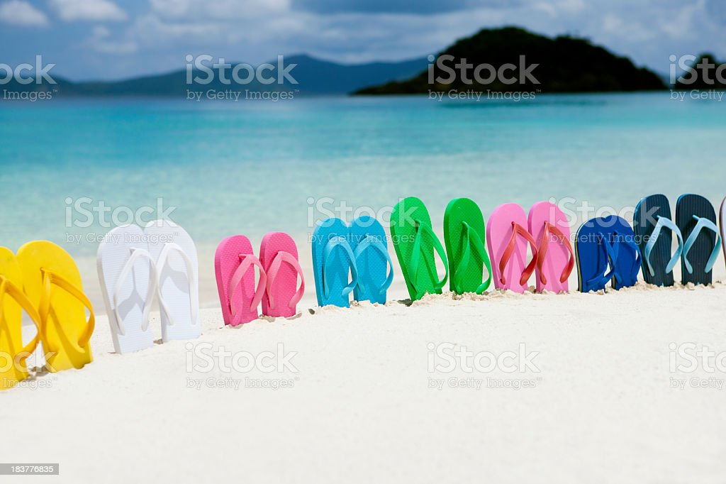 colorful family sandals in white sand on a Caribbean beach royalty-free stock photo
