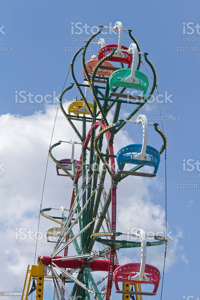 Colorful Ferris Wheel Spins Against a Deep Blue Sky stock photo