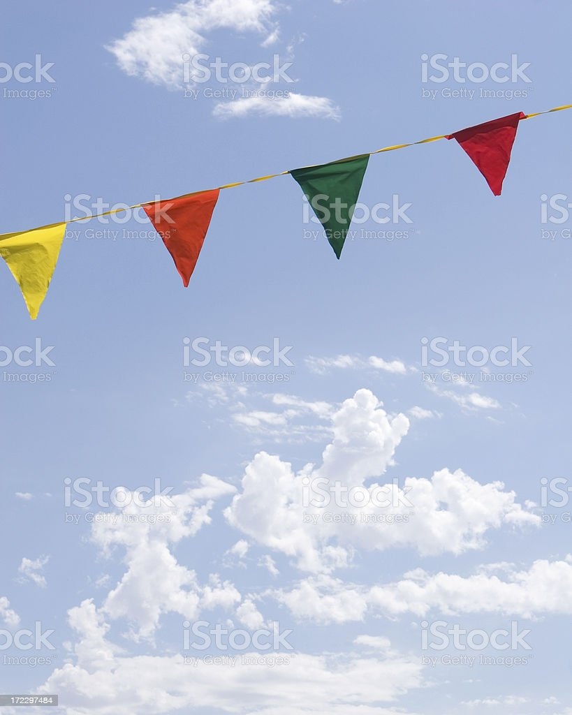 Colorful Festive Flags and Blue Sky with White Clouds stock photo