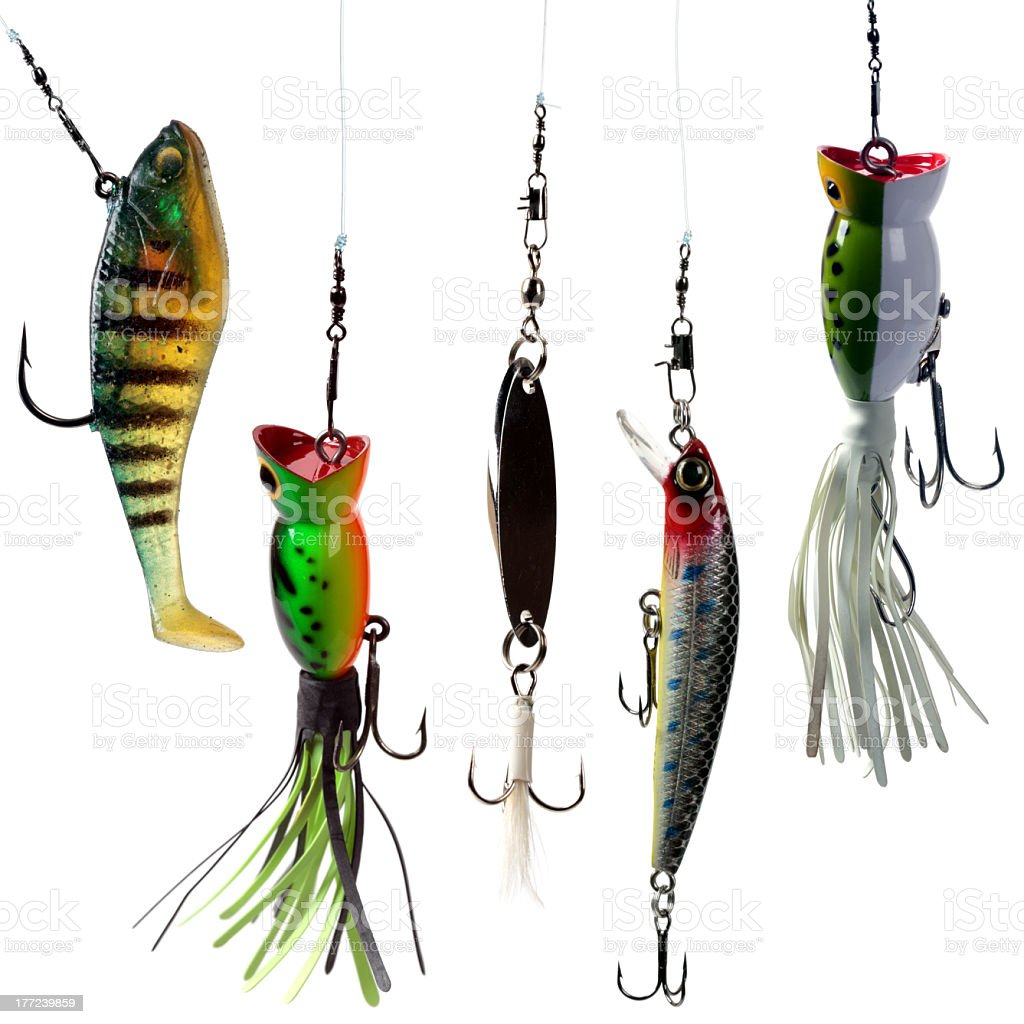Colorful fishing lures dangling against white background stock photo