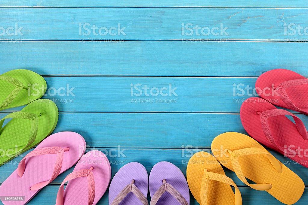 Colorful flip flops atop blue wooden deck stock photo
