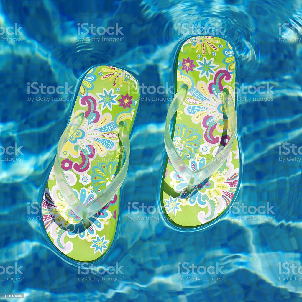 colorful flip-flops floating in a swimming pool royalty-free stock photo