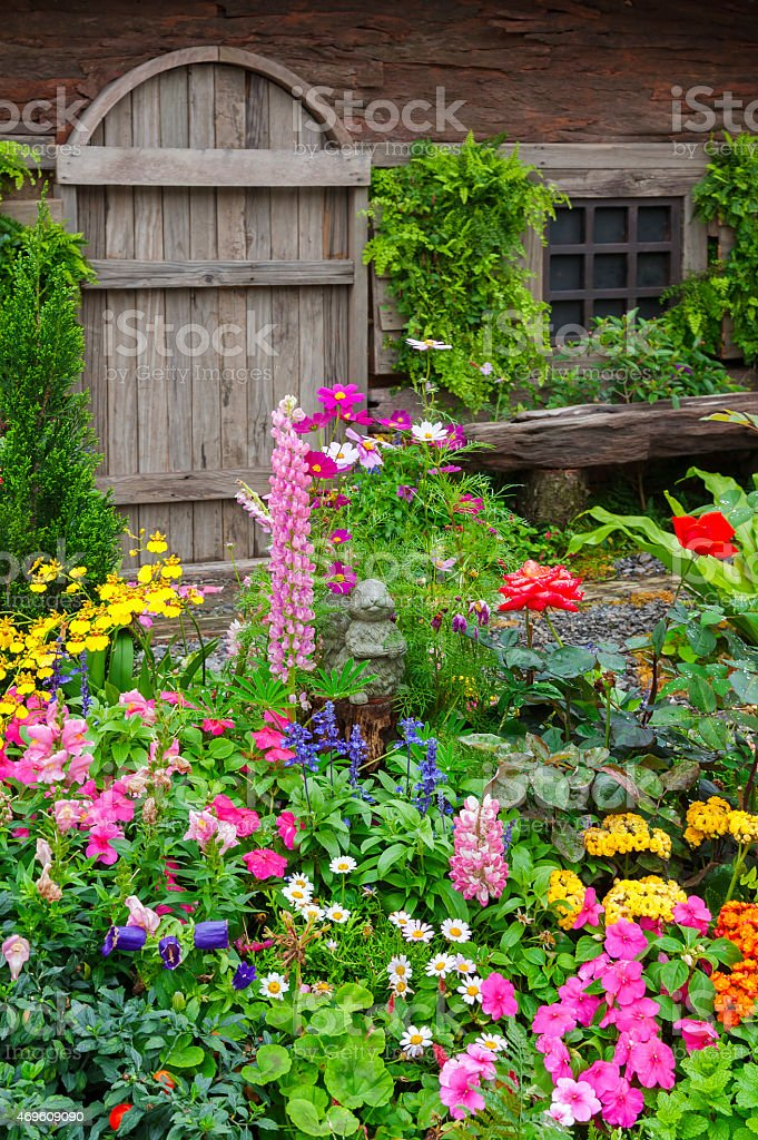 Colorful flower garden in front of cottage stock photo