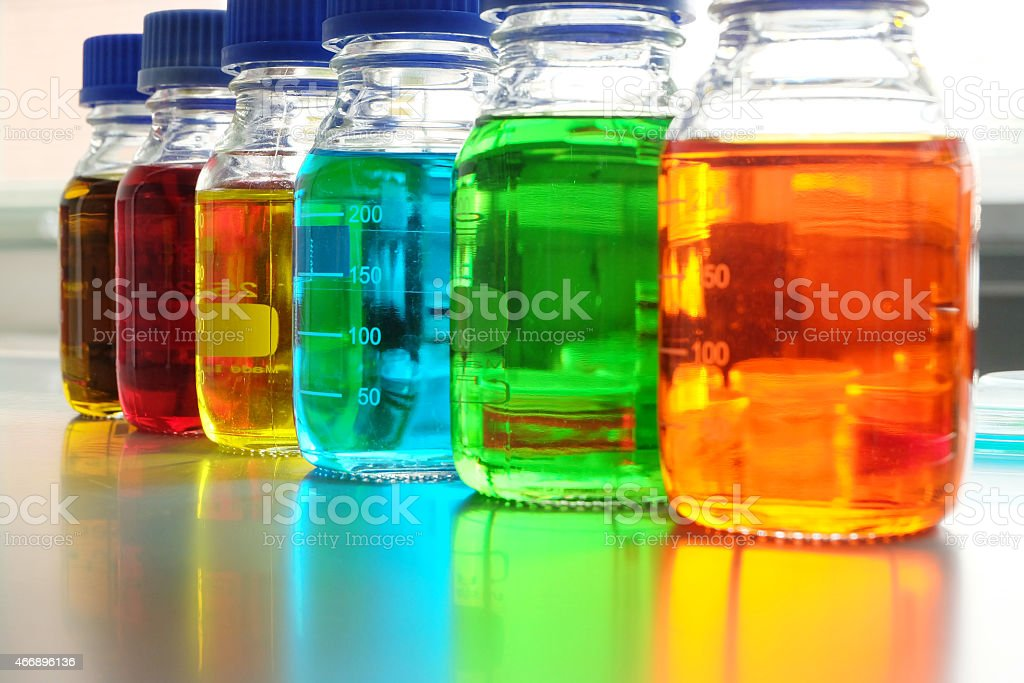Colorful fluid in bottle for laboratory use on the table stock photo