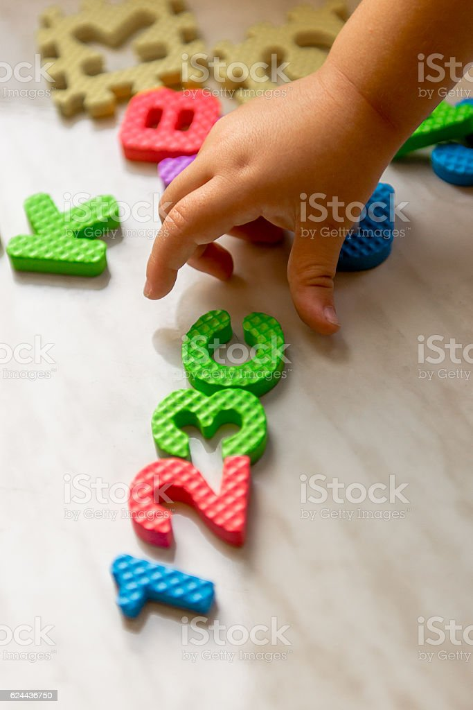 Colorful foam puzzle letters and numbers in kid's hands stock photo