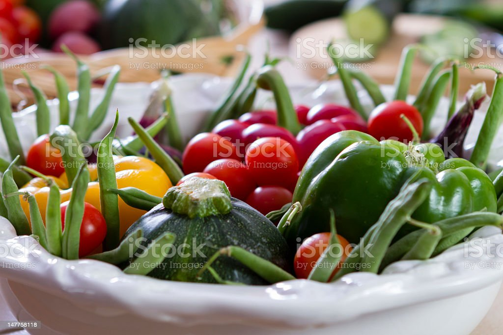 Colorful fresh vegetables fill a white porcelain bowl. stock photo