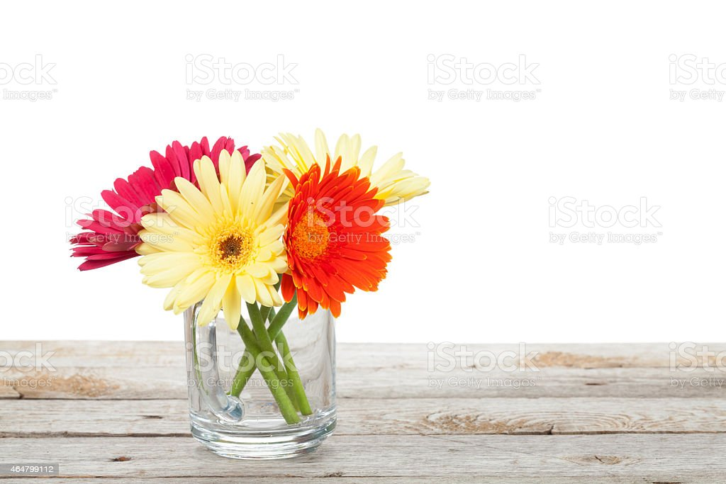 Colorful gerbera flowers on wooden table stock photo