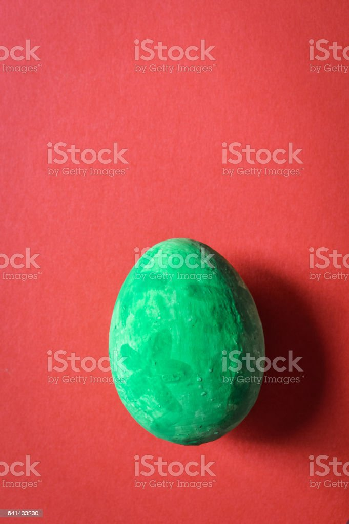 colorful grunge green easter egg on red paper background stock photo