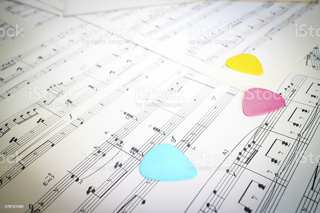 colorful guitar picks on music sheet stock photo