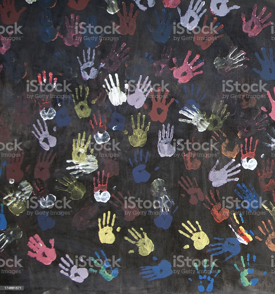 \'colorful children\'s handprints on a textured black wall - fragment...
