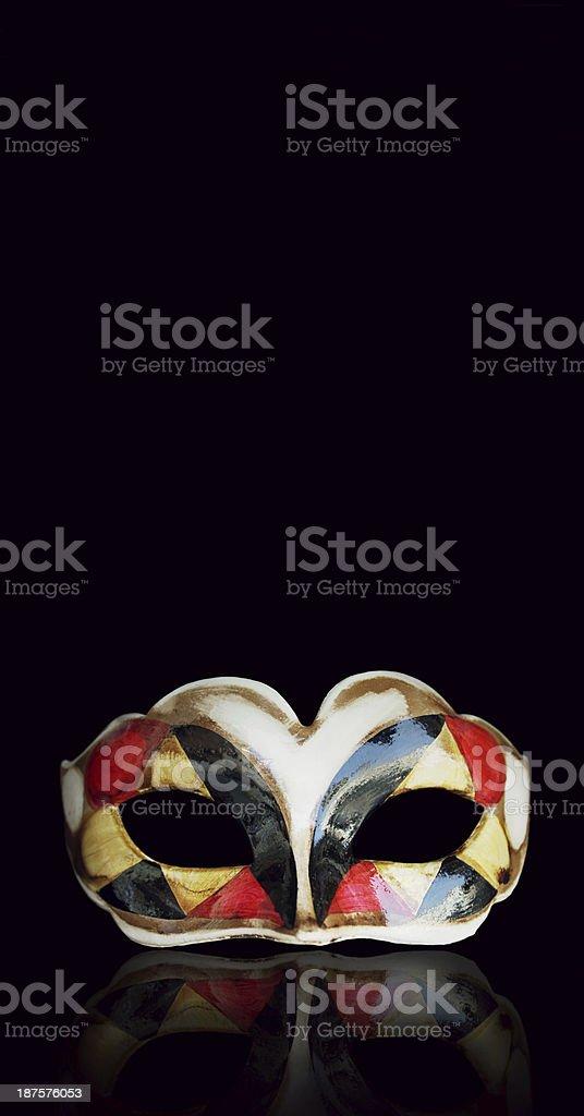 Colorful harlequin mask isolated on dark background stock photo