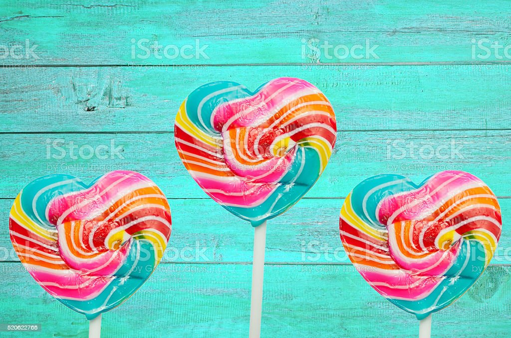 colorful heart lollipop on vintage color wood background stock photo