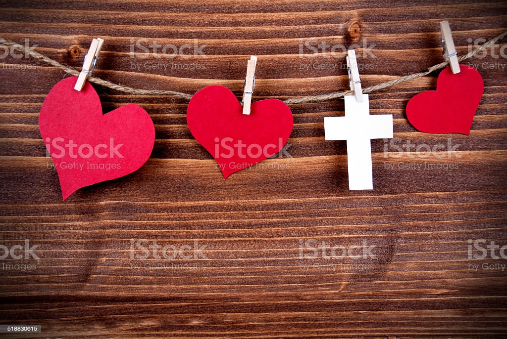 Colorful Hearts and a Cross Hanging on Wooden Background stock photo