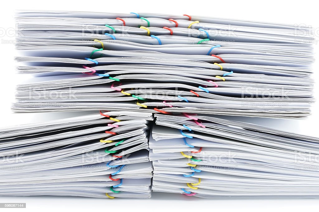 Colorful heart-shaped paperclip on top of pile overload paperwork royalty-free stock photo