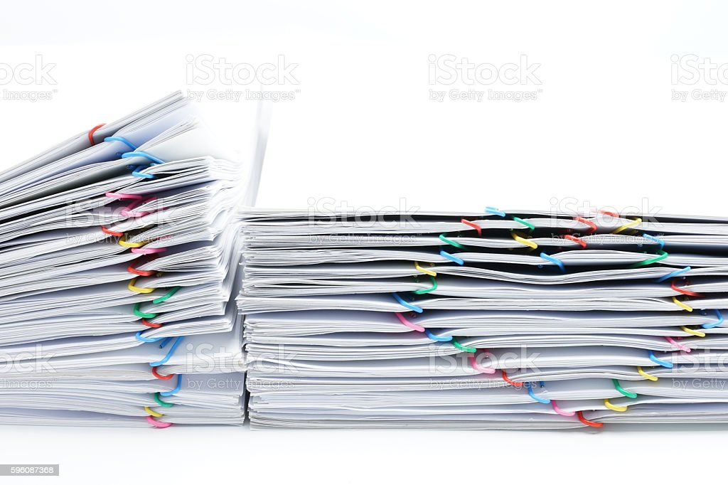 Colorful heart-shaped paperclip placed next to pile overload paperwork royalty-free stock photo