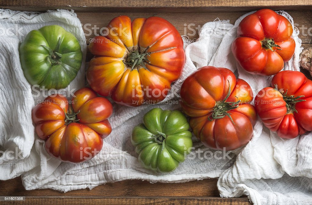 Colorful Heirloom tomatoes in rustic wooden tray stock photo