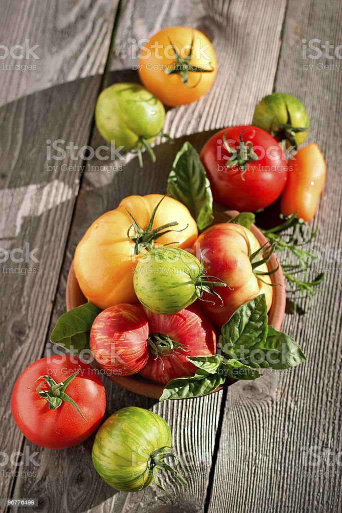 Colorful heirloom tomatoes on a wooden surface stock photo