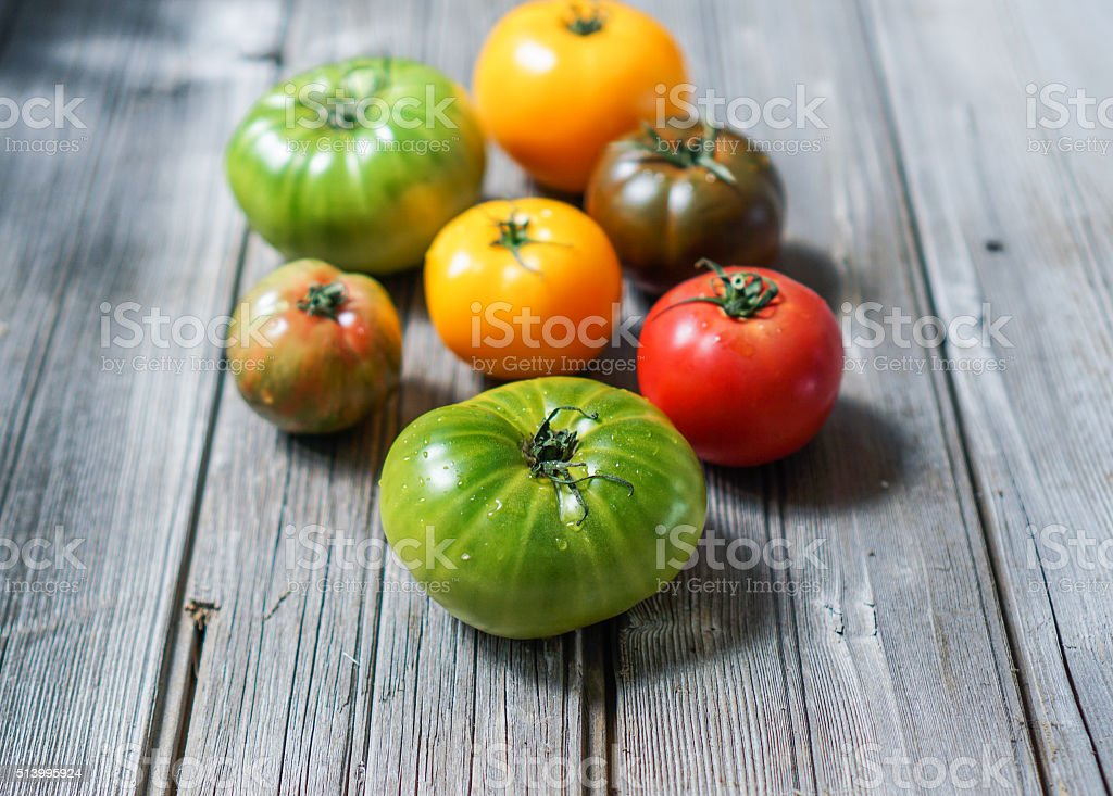 Colorful heirloom tomatoes on wooden background stock photo