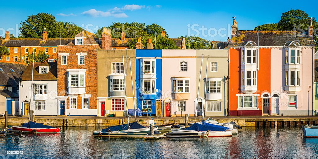 Colorful homes quaint cottages in sunny fishing village harbor panorama stock photo