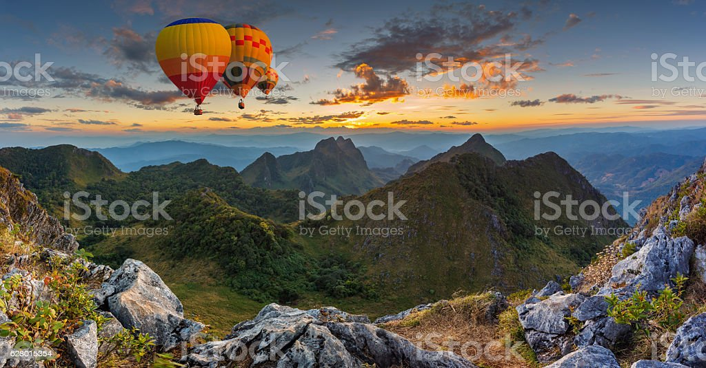 Colorful hot air balloons flying over on mountain stock photo