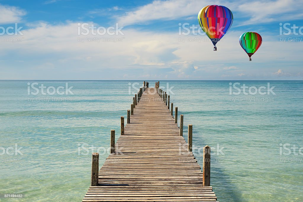 Colorful hot-air balloons flying over Wooden pier in Phuket, Thailand stock photo