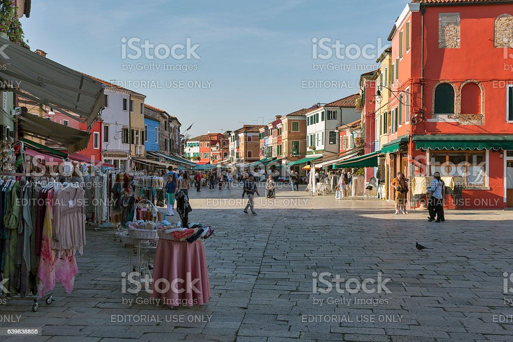Colorful houses and streets with souvenir shop in Burano, Italy. stock photo